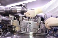 一个人打开一个化学反应器 工业制药的神父 人关闭反应器 生产颗粒化, suspen 免版税库存图片