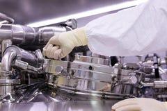 一个人打开一个化学反应器 工业制药的神父 人关闭反应器 生产颗粒化, suspen 免版税库存照片