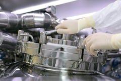 一个人打开一个化学反应器 工业制药的神父 人关闭反应器 生产颗粒化, suspen 免版税图库摄影