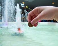 一个人扔硬币入喷泉 库存照片