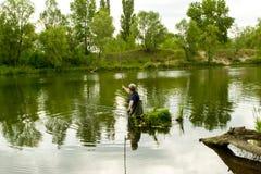 一个人投掷一根钓鱼竿抓鱼 图库摄影