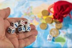 一个人投掷与红色和蓝色标号的模子在世界地图 世界秩序、地图和金钱 库存照片