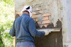 一个人投掷在砖墙上的水泥灰浆 库存图片