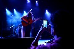 一个人拍与他的智能手机的一张照片在音乐会在Primavera俱乐部2015年节日 库存照片