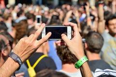 一个人拍与他的智能手机的一张照片在音乐会在生波探侧器节日 库存照片