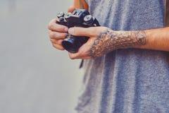 一个人拿着与被刺字的胳膊的一台紧凑影片照相机 库存照片