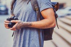 一个人拿着与被刺字的胳膊的一台紧凑影片照相机 免版税库存图片