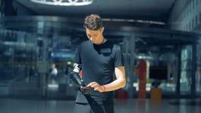 一个人拿着有他计算机控制学的假肢的一个电话,与它一起使用 靠机械装置维持生命的人概念 股票录像