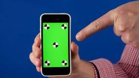 ?? 一个人拿着有绿色色度关键屏幕的一个智能手机和跟踪标志和点在它与他的手指 股票录像