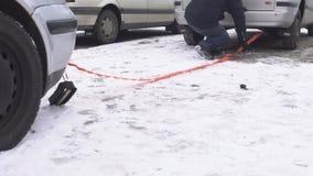 一个人捉住在汽车猛拉,冬天,使用猛拉的zvodka汽车,问题的一拖曳的缆绳 影视素材