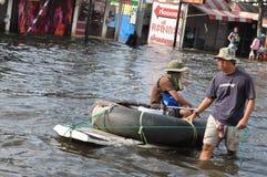 一个人推挤有他的妻子的一个卡车轮胎对此在曼谷,泰国一条被充斥的街道, 2011年11月07日 免版税库存照片