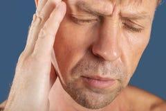 一个人握他的在他的头的手在蓝色背景 头疼或偏头痛 库存图片