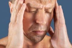 一个人握他的在他的头的手在蓝色背景 头疼或偏头痛 免版税库存图片