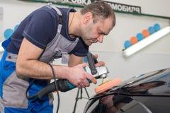 一个人擦亮一辆黑汽车 库存照片