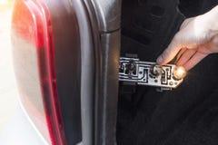 一个人改变在汽车,特写镜头的后方的一个电灯泡 库存照片