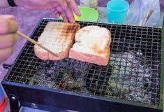 一个人敬酒在多士炉的面包 在面包的重点 库存图片