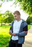 一个人是一位运动员本质上,一条街道在城市,写消息在社会网络 在夏天在公园 库存照片