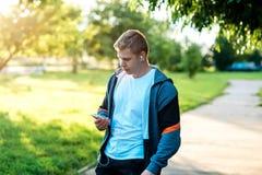 一个人是一位运动员本质上,一条街道在城市,写消息在社会网络 在夏天在公园 免版税库存照片