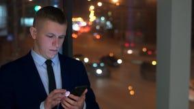一个人是商人,在窗口附近检查他的在他的智能手机的邮件,与夜城市 影视素材