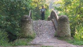 一个人是运动员,带领一种健康生活方式 他横跨桥梁跑,在公园在一个夏日 影视素材