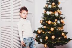一个人有时髦的易洛魁族的理发的和时兴的现代衣裳的在白色墙壁附近站立在圣诞树旁边 A.c. 免版税库存照片