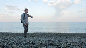 一个人沿海滩走并且在海洋附近检查在巧妙的手表的消息 他是负责任的在社交 股票视频