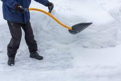 一个人清洗雪在围场与铁锹在以后大雪 库存图片