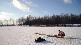 一个人潜水入孔在一冷淡的天,在突然显现霜的一个清楚的冬日,俄国传统在冬天游泳, 股票视频