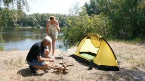 一个人点燃火 女孩给帐篷带来椅子 旅游业,旅行,绿色旅游业概念 河和森林 股票录像