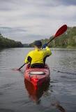 一个人用浆划一艘红色皮船 免版税库存照片