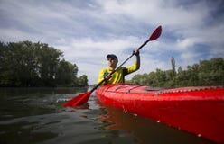 一个人用浆划一艘红色皮船 免版税库存图片