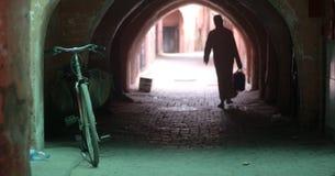 一个人留下他的自行车并且通过入老镇的隧道 库存图片