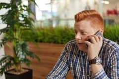 一个人的一张斜向一边的画象有时髦佩带被检查的衬衣和手表的理发和红色头发的坐在caf的绿色种植园附近 免版税库存图片