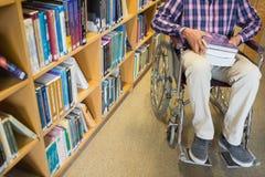 一个人的低部分轮椅的在图书馆里 库存图片