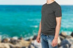 一个人的侧视图一件深灰T恤杉和牛仔布的 库存图片