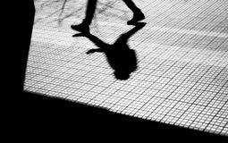 一个人的剪影和阴影城市边路的 免版税库存照片