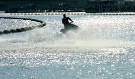 一个人的剪影喷气机滑雪的在有水splashe的海 库存图片