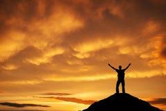 一个人的剪影在山上面的反对日落天空 免版税库存照片