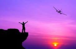 一个人的剪影在岩石和剪影民航飞机上的 免版税库存图片