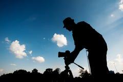 一个人的剪影有照相机的在天空背景 图库摄影