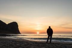 一个人的剪影美好的日落的在Unstad海滩 冲浪者在背景中 免版税图库摄影