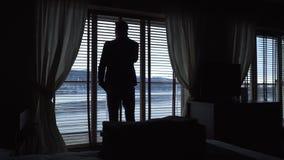 一个人的剪影谈话在手机,当站立在酒店房间在与窗帘时的窗口旁边 股票视频
