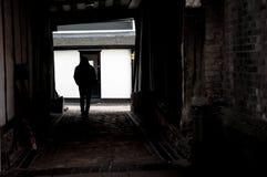 一个人的图一个胡同的在阴影 免版税库存图片