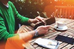 一个人的在触摸板的手键盘输入的播种的射击视图,当坐在边路咖啡馆在夏日时 库存照片