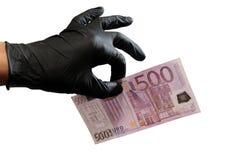 一个人的左手一副黑橡胶手套的拿着与两个手指的五百欧元 背景查出的白色 免版税库存照片