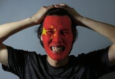 一个人的快乐的画象有中国的旗子的在他的在灰色背景的面孔绘了 体育或民族主义的概念 库存照片