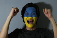 一个人的快乐的画象有乌克兰的旗子的在他的在灰色背景的面孔绘了 体育或民族主义的概念 免版税库存图片