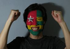 一个人的快乐的画象有多哥的旗子的在他的在灰色背景的面孔绘了 体育或民族主义的概念 免版税库存照片