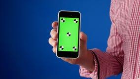 ?? 一个人的手一件红色衬衣的在照相机,有关键绿色的色度的智能手机出现并且做猛击 股票录像