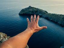 一个人的手反对海和山的 库存照片